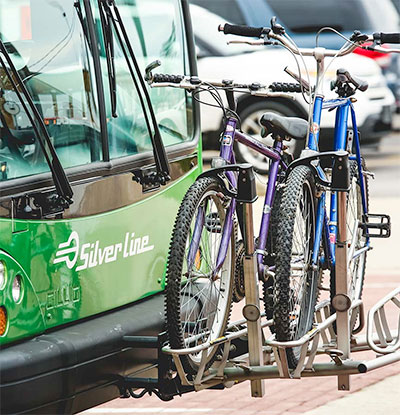 Two bikes loaded on the front of a silver line bus